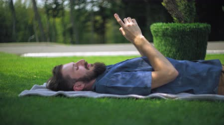 борода : Young happy brunette guy in a blue shirt with a beard lying on blankets in a park on a sunny summer day. Typing messages on the mobile phone and smiling.