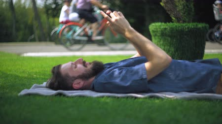 борода : A young guy with a beard lying on blankets on the grass in the park and  a message on the phone. He smiles. Next passing cyclists. Стоковые видеозаписи