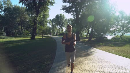 применения : Handsome young man in headphones and sportswear running in the park, where walking woman with dogs and running other people. Mixed race jogger at summer day jogging in the morning outdoors, green trees.