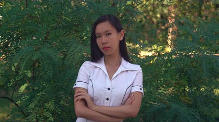 haughty : Successful asian woman standing outdoors. Young professional businesswoman looking at the camera with smile. Female wearing in casual shirt with short sleeves stands in the park in summer season. Her long black hair shine on sun