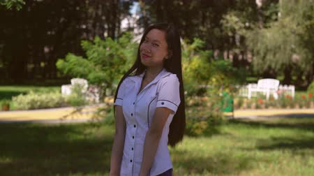 смущенный : Young woman flirtatiously smile at the camera. Asian student standing in front of green tree. Embarrassed attractive girl smiling.Businesswoman wearing in formal shirt with short sleeves stands in the park. Her beautiful long black hair shining Стоковые видеозаписи