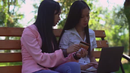alışveriş : Two asian attractive woman buy online sitting on the bench in the park. Happy women shopping via internet use laptop at the open air. Cute girl holding credit card in hands. Smiling friends pay for tickets using wifi. Female with long black hair wearing i