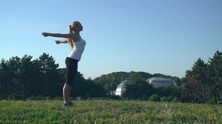 persone : woman raising her hands. Beautiful athlete warming - up body before workout. Caucasian girl with long blond hair stretch muscles in the park. blonde doing exercises for arms stand on the meadow in the forest. Happy sportswoman wearing in sport training bl Stock Footage
