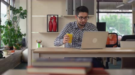 ügynökség : Young professional businessman working in the modern spacious office. Casual man using computer typing on keyboard sitting at the working place drinking orange juice. Mixed race worker looking on the screen wearing in casual shirt.