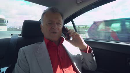 inside car : Portrait middle age businessman sitting on the backseat in the car. aged man sits on a seat at the back of a vehicle using mobile phone. Happy male in years talking on the smartphone drive on the bridge. By him ride different cars. A stream of heavy traff