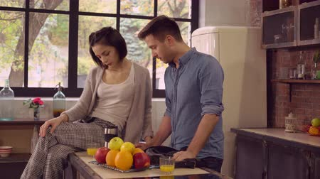 поздний завтрак : happy family on the kitchen in the morning. Young couple in love drinking orange juice at breakfast at home. Attractive woman sitting and talk with handsome man. Guy late for meeting take coffee cup and go away. Cute girl wearing in pajamas husband wearin