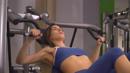 bicep : Woman doing exercises on biceps training machine in gym. Caucasian bodybuilder trains alone. Young beautiful woman working out lifting weights. Girls wearing in blue sport top.