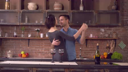 guy home : Couple in love dancing in kitchen. Happy family have fun smiling and enjoy evening in flat. Adult nice woman wearing in elegant dress. Handsome caucasian man dressed in jeans and blue shirt. On the table two glass with red wine and bottle.