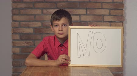 flip chart : Little boy showing whiteboard with handwriting word no. Schoolboy shows sign disagreement waving his head. Preadolescent wearing in casual red shirt.
