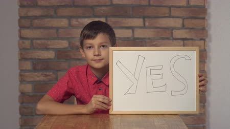 evet : Little boy showing whiteboard with handwriting word yes. Schoolboy shows sign agreement nods his head. Preadolescent wearing in casual red shirt.