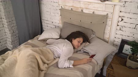 probudit : Brunette using smartphone and continued to sleep. Young woman sleeping in bedroom. Attractive lady wearing in sleepwear hiding the phone under the pillow. Adult girl lying in bed wearing in white casual sleepwear.