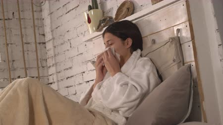 společenská místnost : Woman with rheum ill in flat. Young woman with common cold lying in bed at home. Caucasian girl has a runny nose using napkins in bedroom.