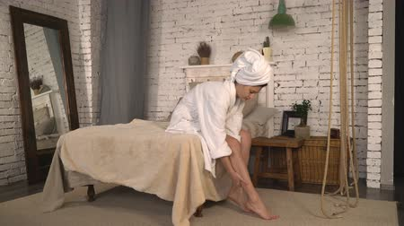pleťová voda : woman rubs legs with cream after bathroom. Lady sitting in bed wearing in white bathrobe with towel on head holding bottle with lotion for body in bedroom with loft interior.