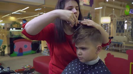 fryzjerstwo : Mens barber cutting hair little boy. Cute kid sitting on chair in barbershop. Brunette hairdresser at working place with client. Upset kid in hairdressing salon. Wideo