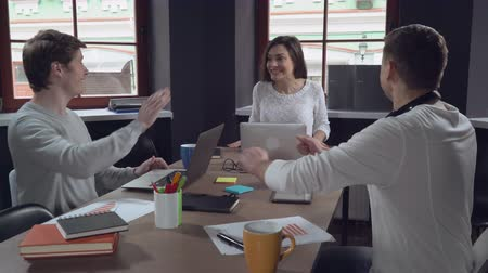 kutluyor : Business team celebrating victory in the office. Young successful colleagues in startup company glad cry and give five each other at work. Handsome men and happy woman make a deal. Female manager received a letter with happy news.