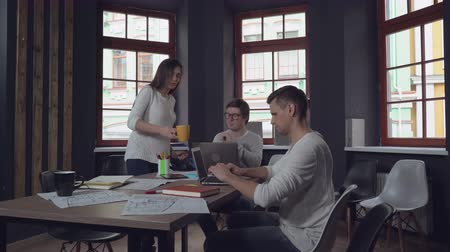 рабочих мест : Young professional woman coming in the room holding two cups with coffee. Hard day in startup company. Casual colleagues focused at project in contemporary office. Two men co workers sitting at the working place typing on computer.