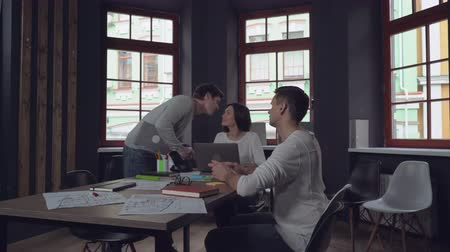 Войти : Morning in startup company office. Professional caucasian guy greets with friends colleagues. shakes hands with a man and kiss on the cheek woman. Businesswoman and businessman sitting at the working place using modern gadgets. Happy young co worker come  Стоковые видеозаписи