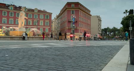 lafayette : town square in nice france. People cross the road at traffic signal. fountain in historic center. tram rides in the evening. time lapse