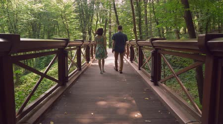 браслет : rear back view girl and guy wearing in summer casual clothes walking on the bridge in forest or park.