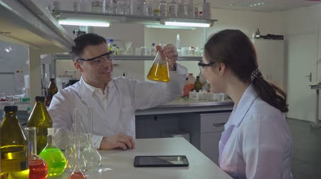 рабочих мест : happy scientist teaching young assistant or student how conduct an experiment. Woman and man discussing results.