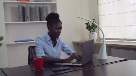 afro amerikai : Afro american businesswoman working in office. Young professional woman sitting at the working place typing on computer. Happy manager chatting online or entering data on laptop.