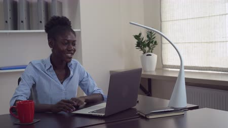 partnerstwo : Young businesswoman has video conference call with partner or friend. Afro american manager greeting interlocutor speaking with happy smile using laptop. Cute woman sitting at the working place in contemporary office wearing casual clothes.