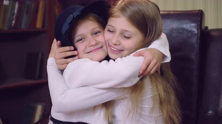 сестра : Portrait two Caucasian sisters with blond long hair embrace one another with happy smile. Smiling small girls neck indoors. sisterly love concept.