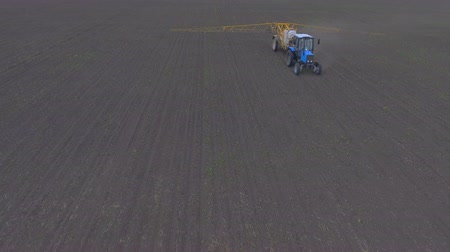 avançar : The tractor spreads fertilizer through the field, shooting from the air. The camera quickly moves away from the tractor by switching to a super overall plan. Stock Footage