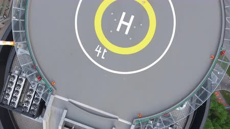 heliport : The helicopter is slowly flying over the modern business center on the roof of a group of air conditioners, a helicopter landing pad with a yellow circle, and below is a road with cars and a green park. Stock Footage