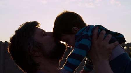 отцовство : Portrait happy adult father with beard kissing son outdoors. Cheerful happy man holding child. Small boy looking on dad and smiling. Blissful fatherhood outdoors at sunset.