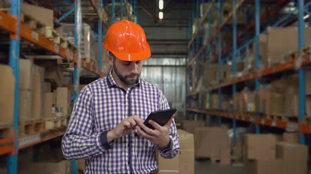gerente : Manager working at warehouse. Handsome young man wearing casual shirt and hard hat using digital tablet entering data. Worker counting box for delivery.