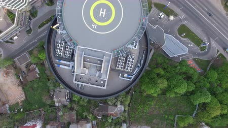 heliport : Aerial shot on the helipad. Top view on the urban landscape in the city with cars rides on the road, modern buildings and green trees.