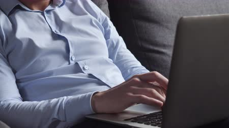 persone : Close up details male hands typing on laptop. Unrecognizable man sitting on sofa wearing blue shirt surfing internet on computer. Stock Footage