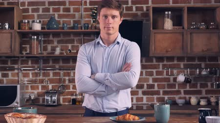 persone : Young caucasian businessman posing looking at the camera in kitchen apartment. Handsome millennial man at breakfast time in flat.
