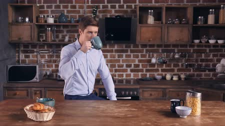 persone : Focused young man drinking coffee sitting in the kitchen at home. Caucasian businessman relish drink before hard day. Guy wearing elegant formal clothes. Stock Footage