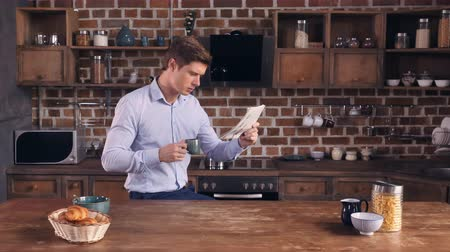 persone : Handsome man caucasian wearing elegant blue shirt enjoy coffee morning time in apartment.Young businessman drinking coffee reading newspaper in the kitchen at home.
