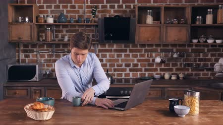 persone : Young businessman at home in the morning. Caucasian man using computer drinking coffee in the kitchen. Guy working in flat reading digital news or documents on laptop.