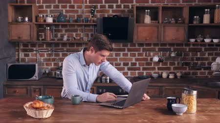 persone : Portrait young businessman working with laptop at home. Handsome caucasian man sitting in kitchen in the morning in apartment. Adult model wearing elegant clothes typing or chatting or surfing internet using wireless in flat.