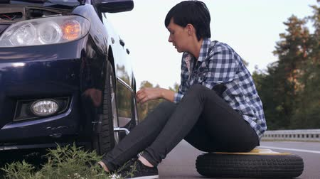 pneus : Young woman stuck on the side of the road with a flat tire. Caucasian brunette driver change a tire at the roadside.