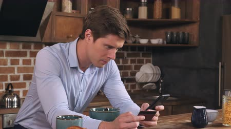 persone : Young businessman holding credit card and smartphone in the morning in kitchen in flat. Handsome man shopping in online store or paying bills at home. Stock Footage