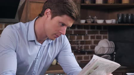 contentamento : Portrait handsome man reading newspaper in the kitchen. Attractive guy in the morning in flat. Stock Footage