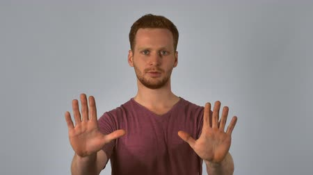 irritate : Portrait young caucasian man on grey background. caucasian guy with red hair posing showing hand gesture stop. handsome redhead men wearing in casual t-shirt
