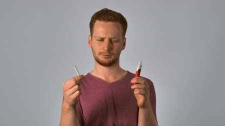 usual : caucasian guy with red hair holding a usual and electronic cigarette. handsome redhead men wearing in casual t-shirt showing problem of choice. portrait young caucasian man on grey background Stock Footage