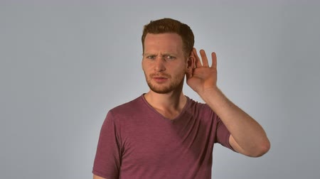 önemseme : caucasian guy with red hair posing showing hand gesture puts his hands to ear and listening. handsome redhead men wearing in casual t-shirt. portrait young caucasian man on grey background Stok Video