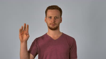 três quarto comprimento : portrait happy young caucasian man on grey background chinese number gestures. caucasian guy with red hair make a gesture with the hand shows the countdown from five to start. handsome redhead men wearing in casual t-shirt Vídeos