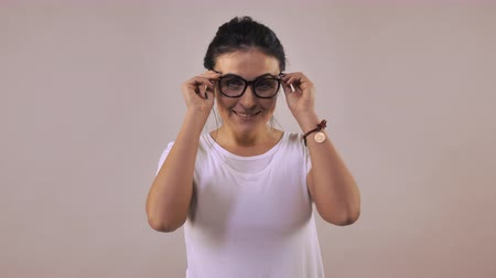 szemüveg : Adult caucasian woman with black hair put on eyeglasses fold ones arms. Portrait young girl wearing casual white t-shirt