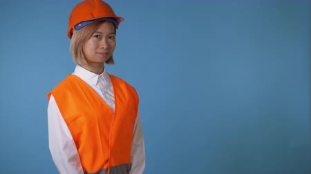 okey : portrait young asian female posing wearing orange hard hat vest showing hand gesture thumbs up on blue background in studio. attractive korean woman with blond hair wearing white casual shirt looking at the camera smiling