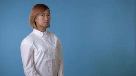 önemseme : close up face young asian businesswoman posing showing hand gesture listening you on blue background in studio. attractive korean woman with blond hair wearing white casual shirt looking at the camera Stok Video