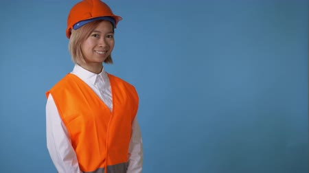 hat : portrait young asian female posing wearing uniform orange hard hat and vest waving hand say hello on blue background in studio. attractive korean woman with blond hair wearing white casual shirt looking at the camera smiling