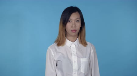 irritate : young asian woman posing showing hand gesture stopping on blue background in studio. attractive millennial girl wearing white casual shirt looking at the camera smiling